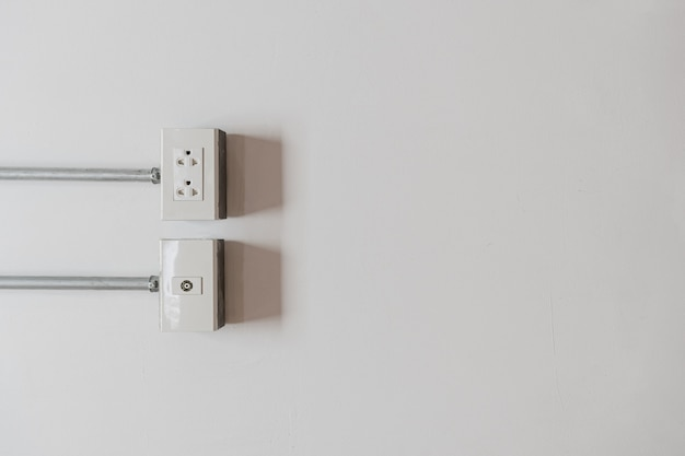 Wall outlet for power cord cable plugged on white wall