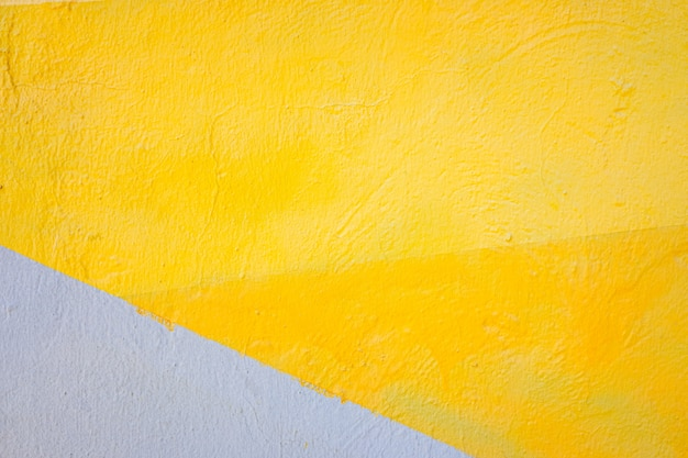 A wall painted with lines of various colors, yellow and orange tones.