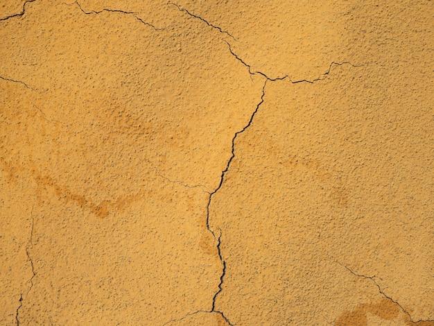 Стена окрашена оранжевой краской с трещинами