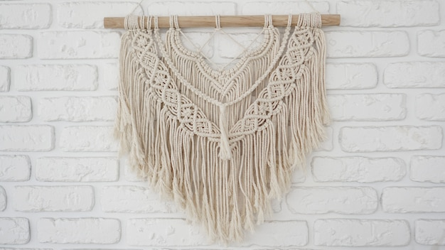 Wall panel in the style of boho made of cotton threads in natural color on a white brick wall. beautiful boho macrame wall panel for a cozy atmosphere