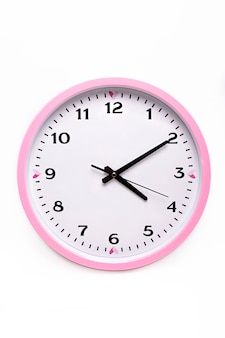 Настенные розовые часы с черным циферблатом на белом фоне.