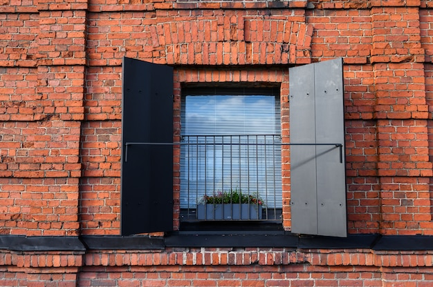 Wall of red brick with a window.