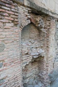 古い生のレンガと石からの壁のテクスチャ。時間によって破壊された古い壁。高品質の写真