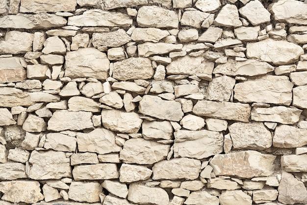 ベージュ色の石積みの壁のテクスチャ。コンセプトの背景、テクスチャ、アーキテクチャ