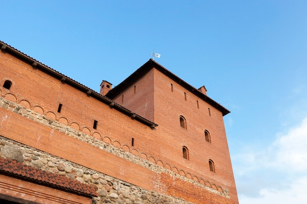 Wall and tower of the fortress, made of red brick, photo of a closeup under a blue sky