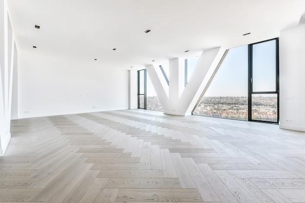 寄木細工の床の豪華なペントハウスアパートメントから街並みを眺める三角形の柱のある壁の窓