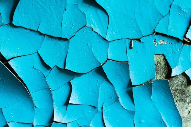 ひび割れに青いペンキが塗られた壁。デザインの背景。グランジテクスチャ。高品質の写真