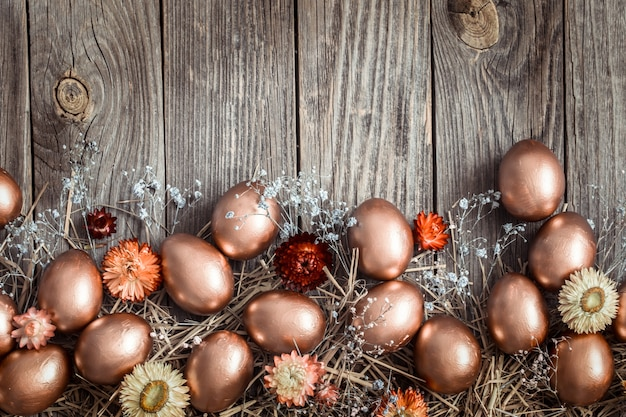 木製の壁に黄金のイースターの卵と壁。