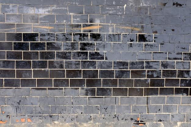 古い黒い光沢のあるタイルの壁。高品質の写真