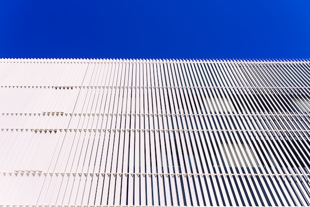 Wall with white metal boards and blue sky background and negative space.