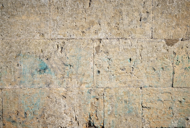 Wall of yellow rectangular stones with cement