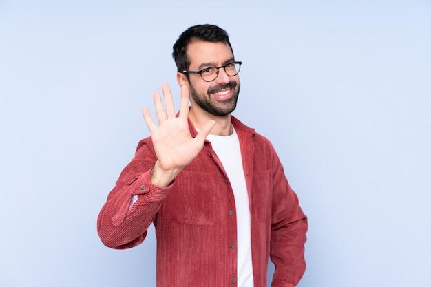 Куртка молодого кавказского человека нося вельвет над голубым wallcounting 5 с пальцами