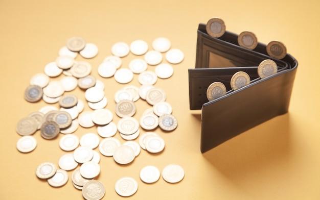Кошелек и монеты на желтом фоне.