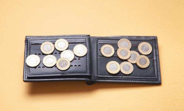 Кошелек и монеты на желтой поверхности.