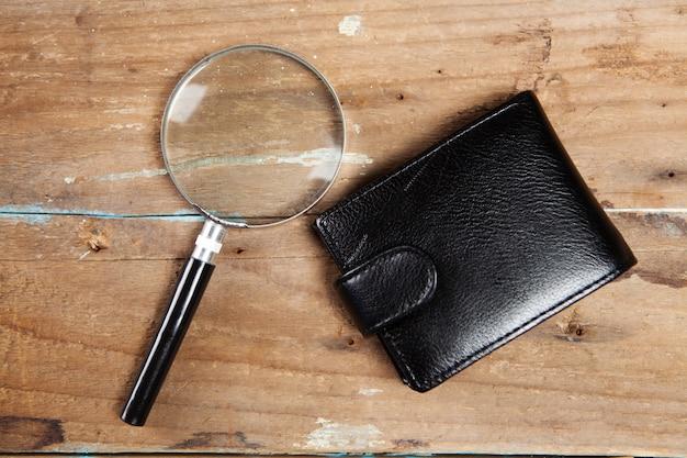나무 표면에 지갑과 돋보기
