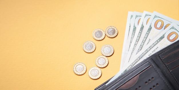 Бумажник, монеты и долларовые банкноты на желтом фоне.