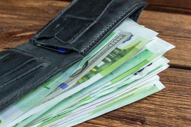 木製の背景にお金の紙幣の財布
