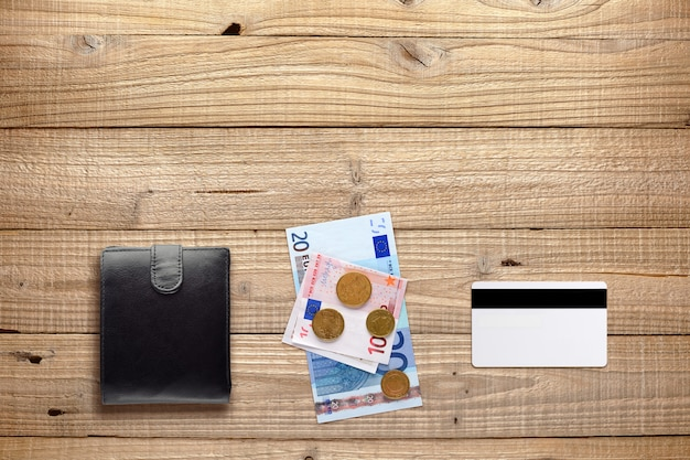 Wallet, money and plastic card on wood