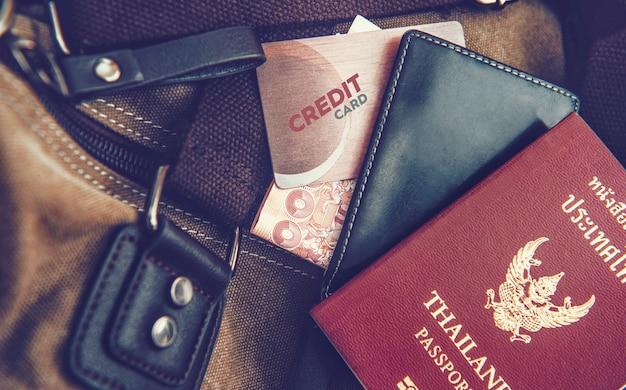 財布、パスポート、袋に置かれたクレジットカード。