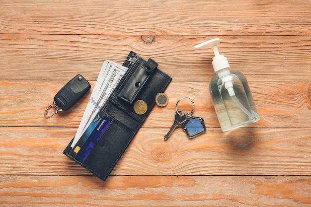 Кошелек с ключами и дезинфицирующим средством на деревянной стене