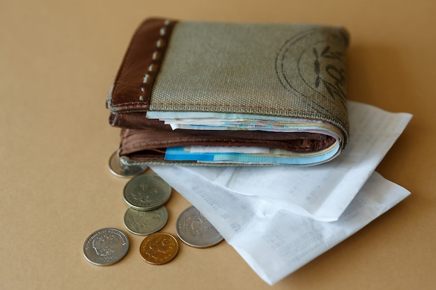 Wallet with money coins and cashiers check from store