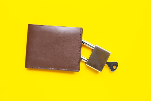 Wallet with padlock and key on yellow table. copy space