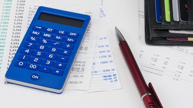 スーパーマーケットのレシートの上に支払いカードと電卓が付いた財布。ショッピングと支払いの概念
