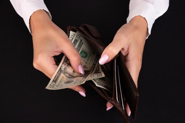 女性の手に米ドルが入った財布