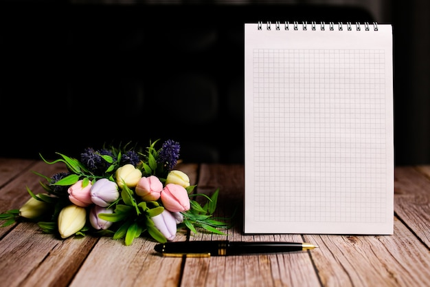 壁紙、おめでとうの背景、テキスト用の空き容量、メモ用のメモ帳、女性のビジネスブロガーのビジネススタイル。国際婦人デー。チューリップの春。高品質の写真