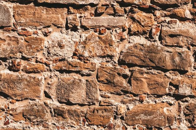 Обои из каменной стены. древний слегка разрушенный камень. флоренция.