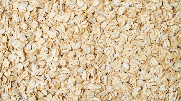Wallpaper of rolled oat flakes cereal whole grain background.