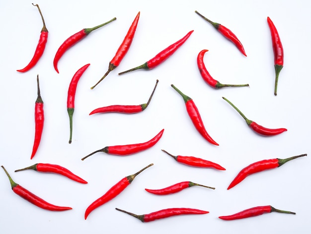 Wallpaper with fresh red hot chili peppers isolated on white wall.