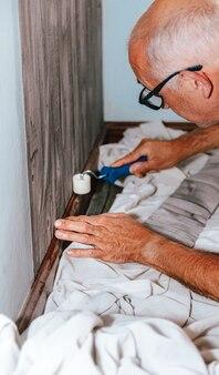 Клеить обои. мужчина клеит серые виниловые обои на флизелиновой основе. ремонт комнаты. оклеивать обоями. ремонт дома.