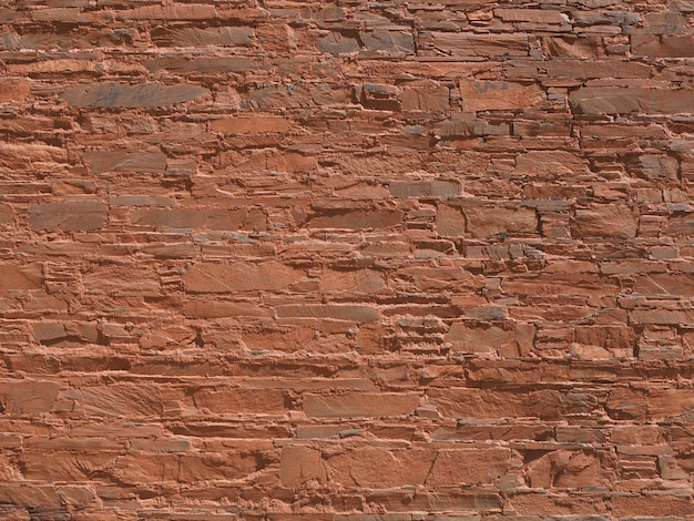 The walls are made of stone, mixed with orange soil.