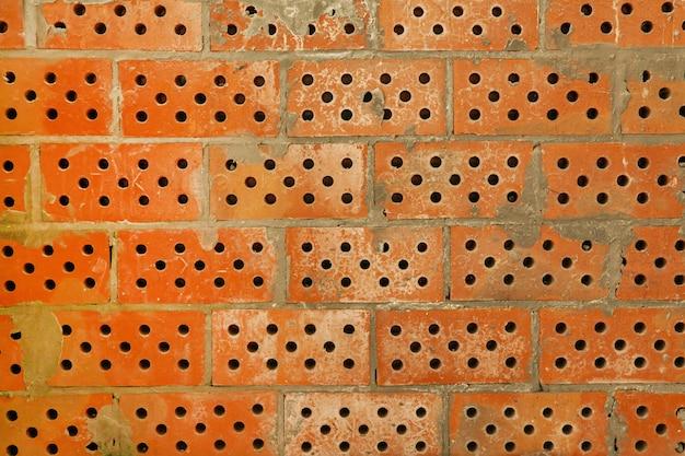 벽은 구멍이 있는 질감이 있는 붉은 점토 벽돌입니다. 시멘트가 있는 새 벽돌집의 배경.
