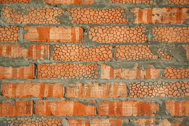 벽은 패턴이 있는 질감 있는 붉은 점토 벽돌입니다. 시멘트가 있는 새 벽돌집의 배경.
