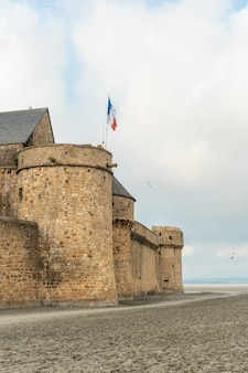 Walls of the famous mont saint-michel abbey at low tide in the manche department, normandy region, france