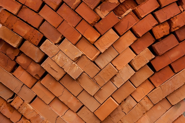 다층 붉은 벽돌 집의 벽입니다. 건설 현장, 도구, 수레, 새 집 건물의 모래 및 벽돌, 시멘트 믹서 기계 및 액세서리