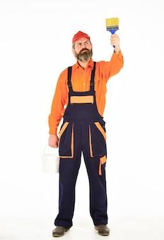 Стены дома отчаянно нуждаются в новой цветовой палитре. художник бородатый зрелый мужчина. художник по стенам с малярным инструментом. художник-хипстер. работают художники. строительство и ремонт. украшение и декор.