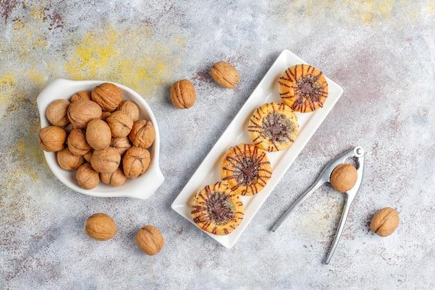 Ореховое и шоколадное печенье с грецкими орехами вокруг, вид сверху