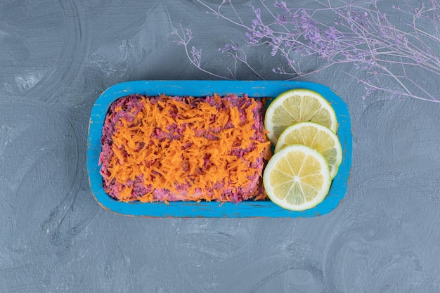Walnut and beet salad topped with carrot and garnished with lemon slices on marble background.