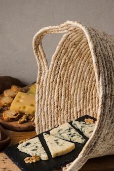 Walnut and blue cheese on black slate in wicker basket