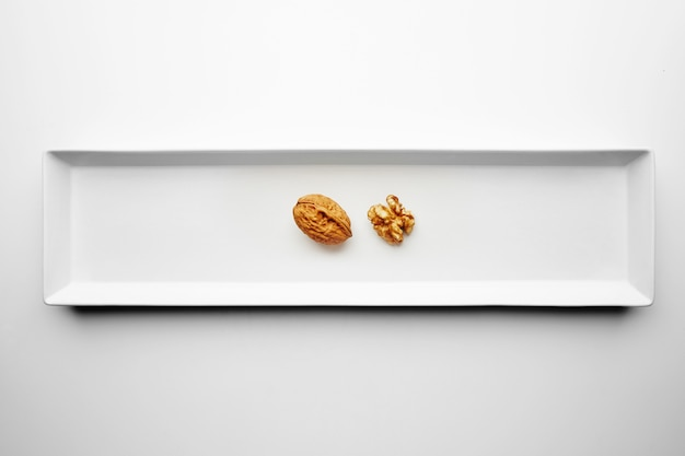 Walnut closed and opened isolated in center of rectangular ceramic plate on white table