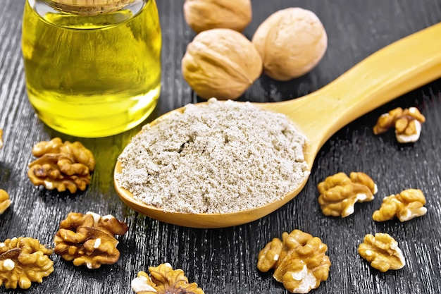 Walnut flour in a spoon, nuts on the table and oil in a glass jar on background of dark wooden board