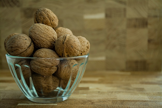 Walnut in a glass bowl on a wooden background.