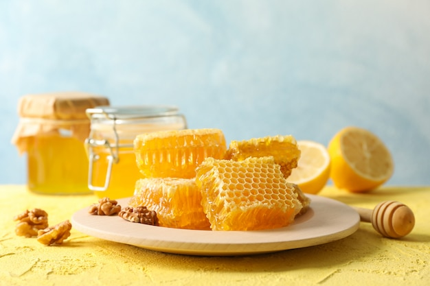 Walnut, honeycombs, jars with honey, dipper and lemon on yellow background, copy space