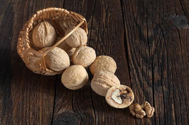 Грецкий орех в корзине и ядра грецких орехов на старом деревянном столе