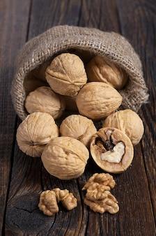 Грецкий орех в мешке и ядра грецких орехов на деревенском старом деревянном столе