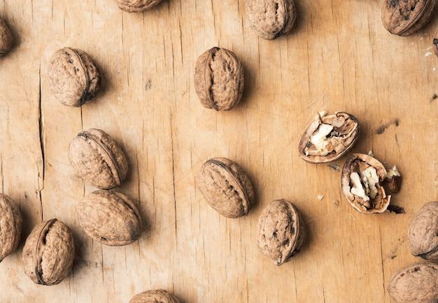 Грецкий орех в скорлупе на деревянном столе, вид сверху