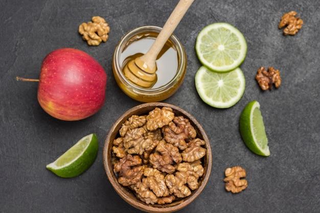 Ядра грецких орехов в деревянной миске, мед в стеклянной банке, целые орехи, ломтики лайма и красное яблоко на столе.
